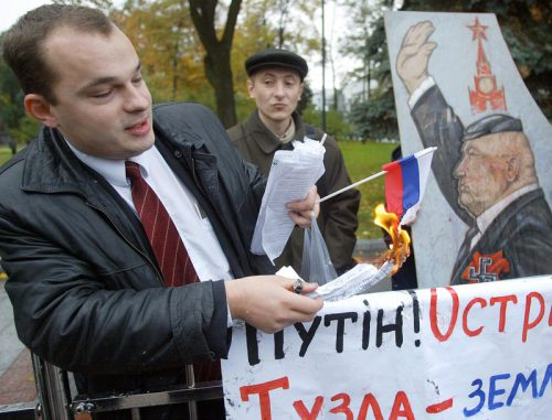 An Ukrainian man sets fire to a Russian flag during a protest in front of the Ukrainian Parliament in Kiev, Wednesday, 22 October 2003 against Russia's construction of a dam near the Ukrainian island of Tuzla. Russian construction of a dam across the Kerch Strait near Ukraine's Crimean peninsula has sparked a war of words for the Ukrainian people. Russian workers in September began intensive construction of a gravel and earth dam in the narrow Kerch strait, at the junction of the Azov and Black Seas. The dam currently is some 400 meters short of waters claimed by Ukraine as territorial waters. EPA/SERGEY DOLZHENKO